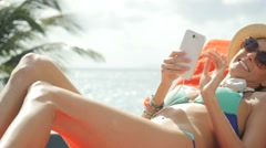 Cheerful funny girl relaxing in long chair with smartphone - stock footage
