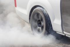 Drag racing car burns rubber off its tires - stock photo