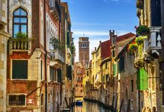 Venice cityscape, narrow water canal, campanile church on background and trad Stock Photos