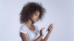 Young biracial girl with mobile phone in studio. Stock Footage