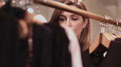 Young adult female looking at clothes in shop Stock Footage