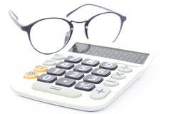 Calculator with eyeglasses isolated on white background - stock photo