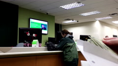People at counter talking to the teller inside TD Bank Stock Footage