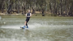 Slow Motion shot of Young Male Adult Wakeboarding on River - Grab Trick Stock Footage