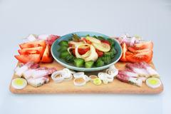 Raw salty pork fat with vegetables on a wooden board Stock Photos