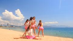 Cheerleaders dance perform high split swing stunt on beach Stock Footage