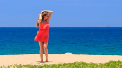 Blond girl in red dances on beach smooths shaken long hair Stock Footage