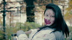 Actress with scary makeup on face chopping at camera with sharp axe, horror film - stock footage