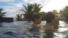 Man playing with kids in swimming-pool Stock Footage