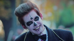 Funny guy with zombie makeup on face standing in street with free hugs sign Stock Footage