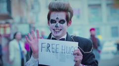 Happy young man with zombie makeup hugging passer-by, flash mob on Halloween Stock Footage