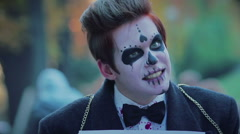 Funny zombie parade in city street, guy with free hugs sign smiling to people Stock Footage