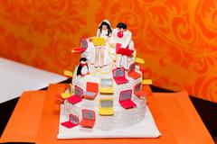Cake figurines of the bride and groom with a laptop Stock Photos