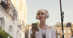 Beautiful blonde listening to music in the city Stock Footage