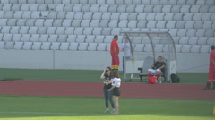 Staff members and paramedics standing on the Cluj Arena field in Cluj-Napoca Stock Footage