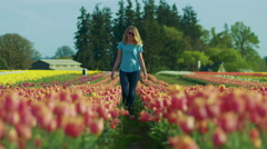 Young teenage girl walking through tulip field toward camera and smiling Stock Footage
