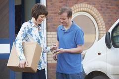 Customer Signing For Delivery From Courier - stock photo