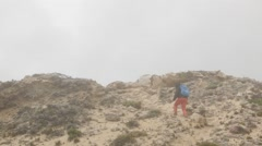 Female hiker walks through rocky landscape Stock Footage