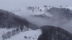 View over the mountains which are loaded with snow with wisps of fog that 722 Stock Footage