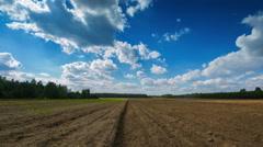 4k timelapse of plowed field under blue cloudy sky Stock Footage
