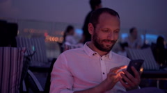 Young man using smartphone and drinking cocktail in bar at night Stock Footage