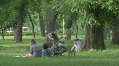 Family with baby relaxing in Central Park, Cluj-Napoca Stock Footage
