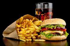 Big single cheeseburger with glass of cola and french fries on black wooden d - stock photo