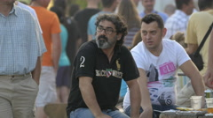 Two men relaxing and talking at River Fest in Cluj-Napoca Stock Footage