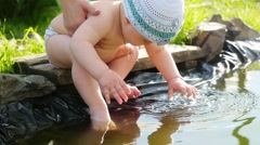 Baby playing in pond outdor in slowmotion. Summer sunset time Stock Footage