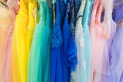 Ladies evening dresses of different colors at shop Stock Photos