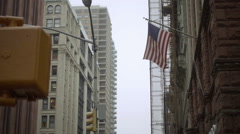 Flag tilting down to American Apparel on East 4th Street and Broadway NoHo NYC Stock Footage