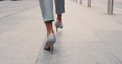 Beautiful mixed race business woman's feet walking through city Stock Footage