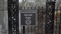 People walking by Washington Square Park sign on south entrance gate gloomy NYC Stock Footage
