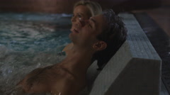 Man and woman are relaxing in the pool on the jacuzzi hot tub plate in spa Stock Footage