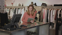Small business owner in clothes shop working on digital tablet - stock footage