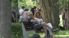 Two friends sitting on a bench in Central Park, Cluj-Napoca Stock Footage