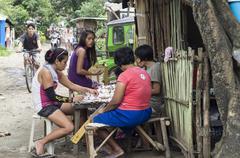 Slum mothers gambling on the street - stock photo