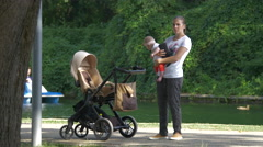 Mother with baby relaxing near the lake in Central Park, Cluj-Napoca Stock Footage