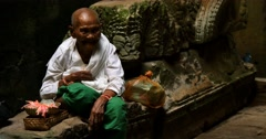 Old man Cambodian beggar monk sitting in temple offering preyer Stock Footage