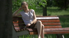 Girl talking on the phone in Central Park, Cluj-Napoca Stock Footage