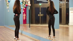 Young sexy dancer and tight tights moves her hips in front of a mirror - stock footage