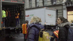 Zooming out movers orange construction vests crating cargo truck Broadway NYC Stock Footage