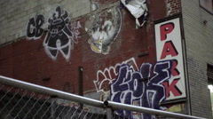 Zooming out from graffiti on brick wall in NoHo on Broadway rainy day people NYC Stock Footage