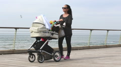 Woman walking along the beach with baby Stock Footage