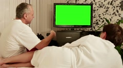 Couple sitting on the couch and watching TV with green screen. - stock footage