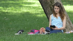 Girl relaxing and reading in Central Park, Cluj-Napoca Stock Footage
