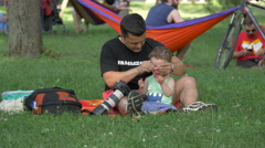Father and son relaxing in Central Park, Cluj-Napoca Stock Footage