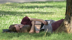 Couple lying on grass in Central Park, Cluj-Napoca Stock Footage