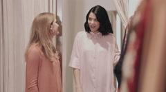 Female friends fitting clothes in boutique Stock Footage
