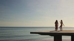 Three girls in bathing suit dancing on the pier Stock Footage